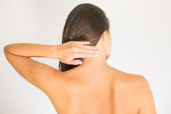 Woman with upper back and neck pain. Standing naked with her back to the camera and her hand rubbing her shoulder muscles close to the spine Stock Photography
