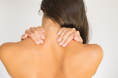 Woman with upper back and neck pain. Standing naked with her back to the camera and her hand rubbing her shoulder muscles close to the spine Stock Photos