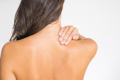 Woman with upper back and neck pain. Standing naked with her back to the camera and her hand rubbing her shoulder muscles close to the spine Royalty Free Stock Photo