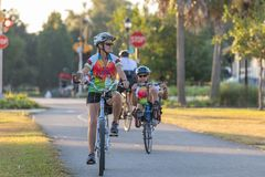 Woman on upright bike with man in background on recumbent bike, editorial. stock photos