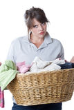 Woman upset doing laundry; isolated. Young woman upset about having to do laundry; isolated a a white background Royalty Free Stock Images