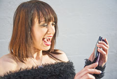 Woman upset by mobile phone message. Royalty Free Stock Photos