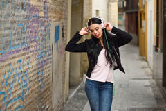 Woman in urban background listening to music with headphones Stock Image