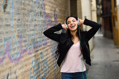 Woman in urban background listening to music with headphones Royalty Free Stock Images