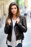 Woman in urban background wearing leather jac. Portrait of beautiful japanese woman in urban background wearing leather jacket Stock Photo