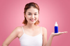 Woman use body lotion on arms and holding cosmetics bottle on pi Stock Image