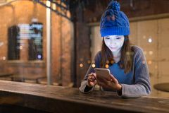 Woman use of cellphone in coffee shop at night. Asian young woman Royalty Free Stock Photography