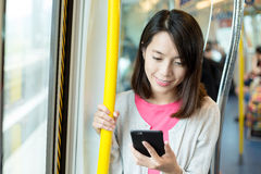 Woman use of cellphone inside train Royalty Free Stock Photography