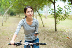 Woman use of cellphone for searching direction while riding bicy Royalty Free Stock Photo