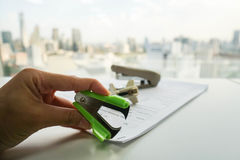 Woman use green staple puller remove staple from document. Woman use green staple puller to remove staple from business document by left hand Stock Images