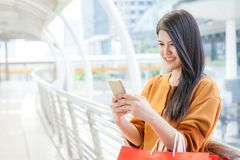 Woman use of mobile phone and carrying paper bags in city.  royalty free stock photography