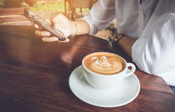 Woman use mobile phone with coffee cup vintage tone. Royalty Free Stock Photo