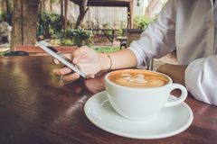 Woman use mobile phone with coffee cup vintage tone. Royalty Free Stock Photography