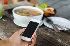 Woman use mobile phone in coffee shop view from backside and meal background. royalty free stock photos
