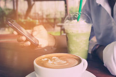 Woman use mobile phone and drink green tea frappe with coffee cup vintage tone. Royalty Free Stock Photography