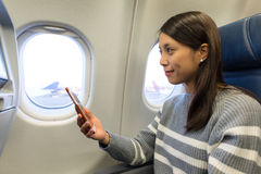 Woman use mobile phone and looking out of the window at plane ca Royalty Free Stock Images
