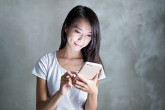 Woman use of mobile phone over grey background royalty free stock photography