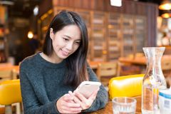 Woman use of mobile phone in restaurant Stock Photo