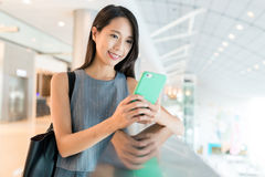 Woman use of mobile phone in shopping mall. Asian young woman Stock Images