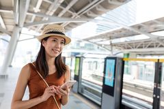 Woman use of mobile phone in train station Stock Image