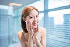 Woman use oil blotting paper. Young asian skin care woman smile and use oil blotting paper on her face royalty free stock images