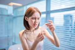 Woman use oil blotting paper. Young asian skin care woman upset after use oil blotting paper on her face stock image