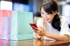 woman use phone with her shopping bag in the restaurant royalty free stock photography