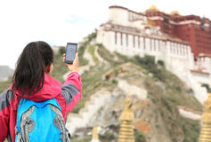 Woman use smart phone taking photo in tibet Royalty Free Stock Photos
