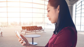 Woman use smartphone in airport. Stock Photos