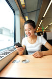 Woman use smartphone interior of train. Young asian woman use smartphone interior of train/subway receives good news Royalty Free Stock Images