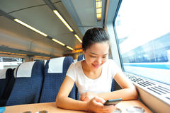 Woman use smartphone interior of train royalty free stock images