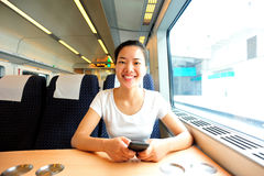 Woman use smartphone interior of train. Young asian woman use smartphone interior of train/subway receives good news Royalty Free Stock Photo