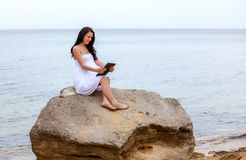 Woman use touch pad tablet pc internet technology sitting beach Stock Photos