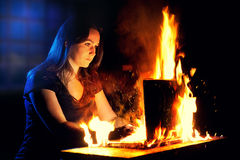 Woman uses a burning laptop Stock Images