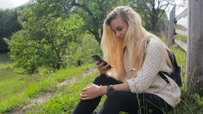 Woman uses cell phone on mountain road stock footage