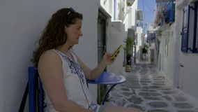 Woman uses a cell phone in the streets of Mykonos. Woman uses a cell phone texting technology in the streets of Mykonos Greece stock video