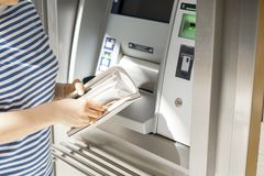 A woman uses a credit card at an ATM on the street. Operation with money. Payment. Copy space royalty free stock photography