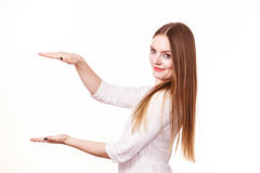 Woman uses hands to indicate area of frame, copy space for product. Woman showing presenting, long haired fashion girl uses hands to indicate area of frame, copy Royalty Free Stock Images