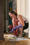 Woman uses heat gun to scrap paint on home trim Stock Photography