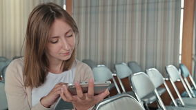 Woman uses her new digital PC tablet in the empty conference hall stock footage