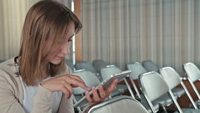 Woman uses her new digital PC tablet in the empty conference hall stock video