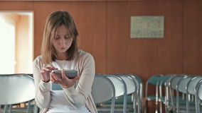 Woman uses her new digital PC tablet in the empty conference hall stock video footage