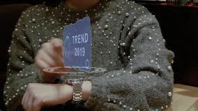 Woman uses hologram watch with text Trend 2019. Unrecognizable woman working with HUD hologram of a smart watch with text Trend 2019. Female hands with future stock video footage