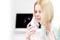 A woman uses an inhaler. Stock Photo