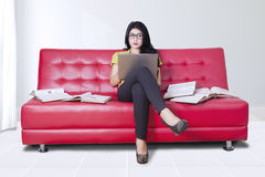 Woman uses laptop with books on sofa Royalty Free Stock Photography