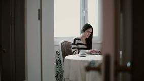 Woman uses laptop and enjoying morning coffee on a bright dining. slider to the left, view through the open doors stock video footage