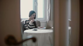 Woman uses laptop and enjoying morning coffee on a bright dining. view through the open doors. Attractive young woman uses laptop and enjoying morning coffee on stock video footage