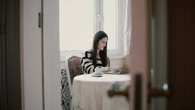 Woman uses laptop and enjoying morning coffee on a bright dining. view through the open doors. Attractive young woman uses laptop and enjoying morning coffee on Royalty Free Stock Photography