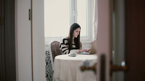 Woman uses laptop and enjoying morning coffee on a bright dining. view through the open doors. Attractive young woman uses laptop and enjoying morning coffee on Royalty Free Stock Image