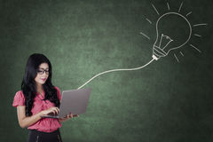 Woman uses laptop with light bulb in classroom Royalty Free Stock Photography